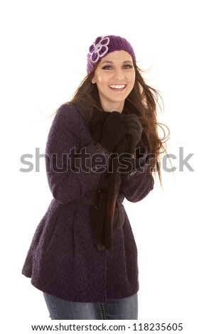 A woman in her winter coat and hat with the wind blowing with a smile on her lips. - stock photo