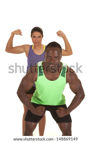 A woman in her workout clothes flexing her arms, while a man in front of her is flexing his. - stock photo