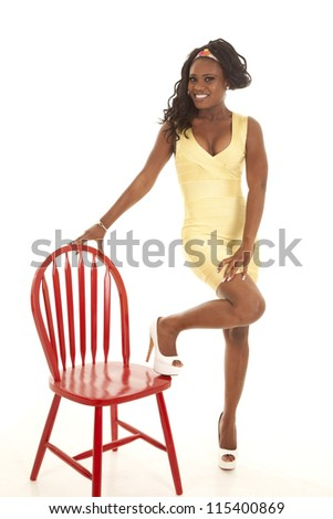 a woman in her yellow dress with one foot up on a red chair with a smile on her face, - stock photo