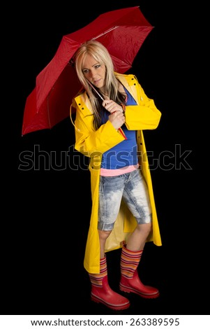A woman in her yellow rain coat, boots and holding her umbrella, looking down. - stock photo
