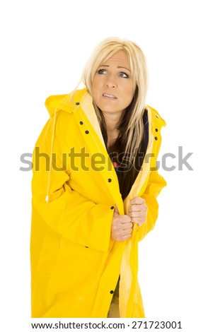 a woman in her yellow rain coat with a frightened expression on her face. - stock photo