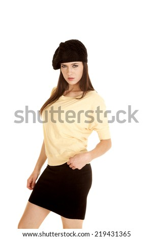 A woman in her yellow top with a black skirt and a french beret on her head.