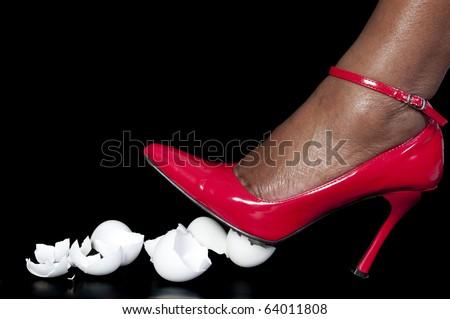 A woman in high heels walking on eggshells - stock photo