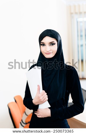 A woman in hijab holding documents while working in the office - stock photo