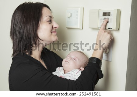 A woman in house who set is thermostat. - stock photo