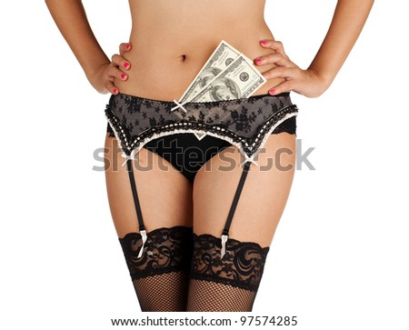 A woman in lace stockings and underwear with money tucked in her stockings. - stock photo