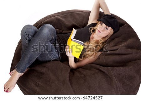 A woman in laying on a bean bag with a book. - stock photo