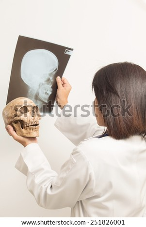 A woman in medical uniform looks at human skull.  and Sheets  X-ray services. on white background on white.  - stock photo