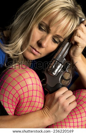 A woman in pink fishnet stockings holding a revolver looking down up close. - stock photo