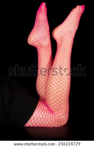 A woman in pink fishnets laying on her stomach close up shot of her legs. - stock photo