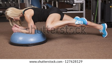 a woman in plank on a half of a ball bringing her knee to her arm. - stock photo