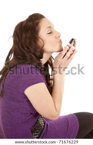 A woman in purple kissing at her cell phone. - stock photo