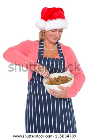 A woman in Santa hat holding a bowl and mixing the ingredients for a Christmas cake, isolated on a white background. - stock photo