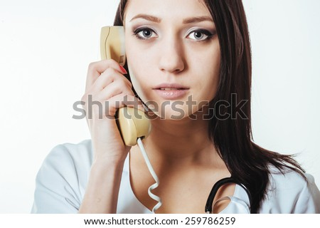 A woman in scrubs holding a telephone. Portrait of confident female doctor using telephone  - stock photo