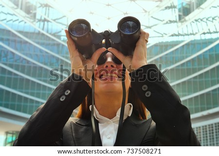 A woman in suits looks at binoculars as a glimpse into the future, future plans and ambitions.