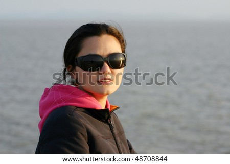 A woman in sunset with sun glasses - stock photo