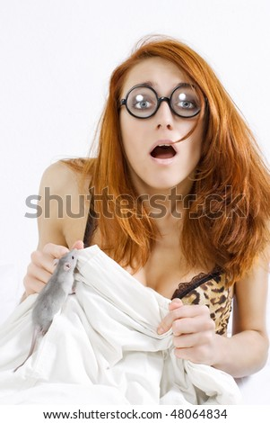 A woman in the bed scared by rat - stock photo