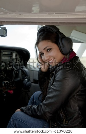 A woman in the cockpit of an airplane smiling. - stock photo