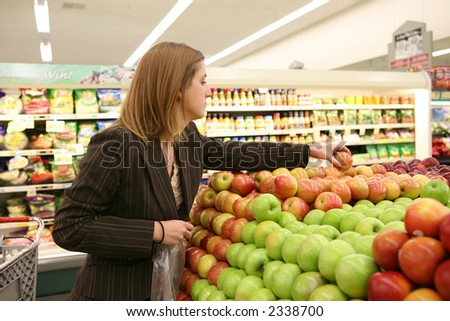 A woman in the grocery store selecting an apple - stock photo