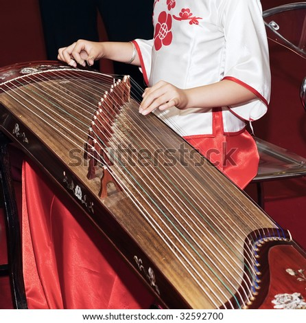 A woman in traditional costume playing guzheng.Guzheng is an traditional Chinese musical instrument,It belongs to the zither family of string instruments. - stock photo