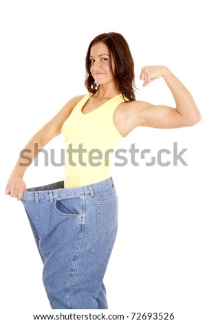 A woman in very large pants and a small waist is showing her muscles. - stock photo