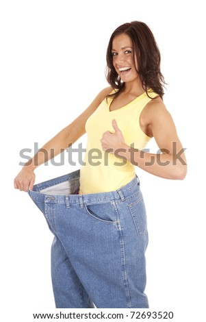 A woman in very large pants is giving a thumbs up - stock photo