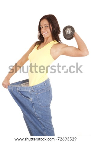 A woman in very large pants is holding a weight up with one arm - stock photo