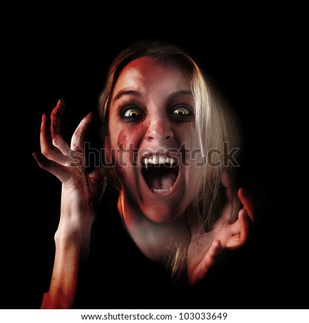 A woman is a scary vampire with pointy teeth and blood all over her hands and face. Use it for a fear or Halloween concept. - stock photo
