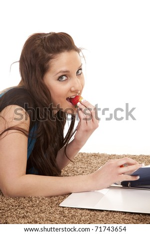 A woman is biting a strawberry while studying.