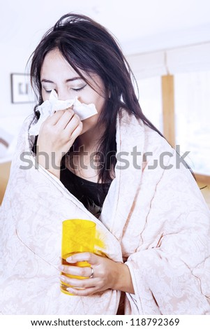 A woman is blowing her nose wrapped in blanket at home - stock photo