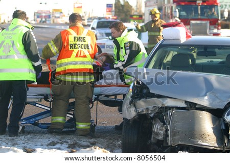 A woman is cared for by emergency workers after a motor vehicle accident in Edmonton,Alberta,Canada. - stock photo