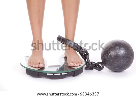A woman is chained to the bathroom scales. - stock photo