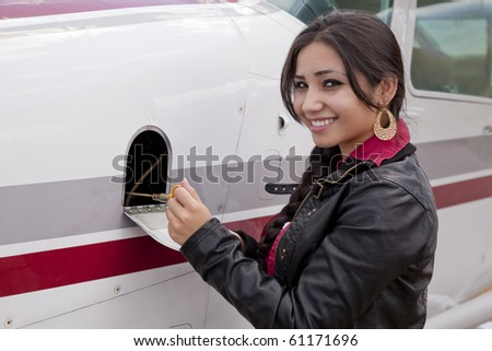 A woman is checking the oil in an airplane. - stock photo
