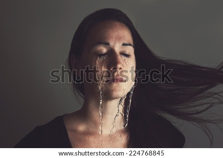 A woman is crying with streams of tears running down her face. - stock photo