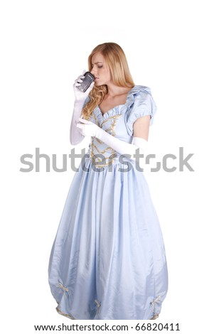 A woman is dressed like Cinderella and is holding a phone to her nose. - stock photo