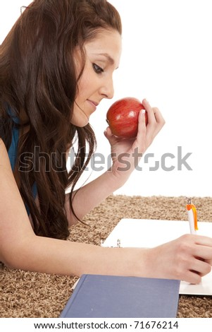A woman is eating an apple and doing homework.