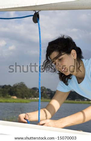 A woman is fixing the sail on their sailboat.  She is looking at the ropes she is pulling.  Vertically framed shot. - stock photo