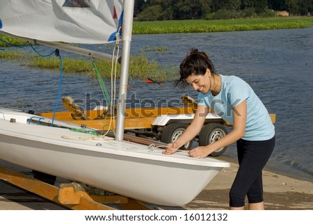 A woman is fixing the sail on their sailboat.  She is smiling and looking at the ropes she is pulling.  Horizontally framed shot. - stock photo