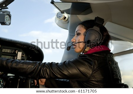 A woman is flying an airplane and messing with the instruments - stock photo