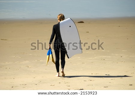 a woman is getting to go into the water to go  surfing with body board - stock photo