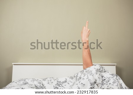 A woman is hiding under the covers in a bed and is displaying an obscene gesture - stock photo