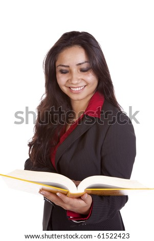 A woman is holding a book and smiling at it. - stock photo