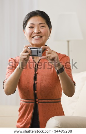 A woman is holding a camera in her hands.  She is smiling at the camera.  Vertically framed shot. - stock photo