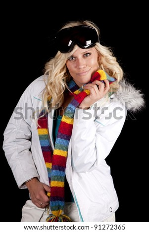 A woman is holding a colorful scarf, a winter coat, and ski goggles. - stock photo