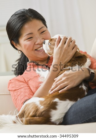 A woman is holding a dog in her arms, smiling, and looking away from the camera.  Vertically framed shot. - stock photo