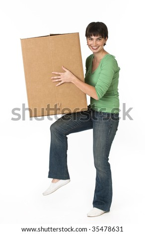 A woman is holding a moving box and smiling at the camera.  Vertically framed shot.