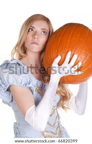 A woman is holding a pumpkin to her ear and listening.  She is dressed like Cinderella. - stock photo