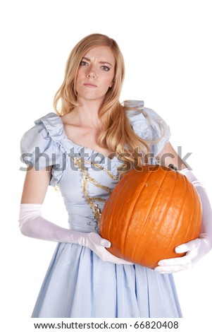 A woman is holding a pumpkin with a look of wonder. - stock photo