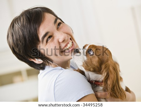 A woman is holding a puppy and smiling at the camera.  Horizontally framed shot.