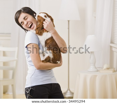 A woman is holding a puppy in her arms and laughing.  Horizontally framed shot. - stock photo